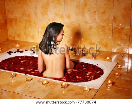 Woman relaxing in bath with rose petal. - stock photo