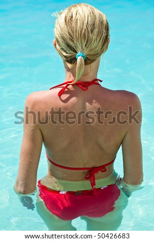Woman relaxing in blue outdoor swimming water-pool