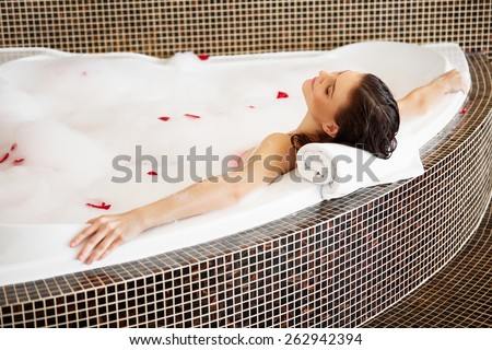 Woman Relaxing in Bubble Bath With Rose Petals. Body Care - stock photo