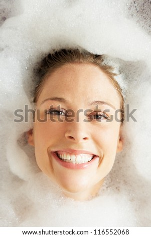 Woman Relaxing In Bubble Filled Bath - stock photo