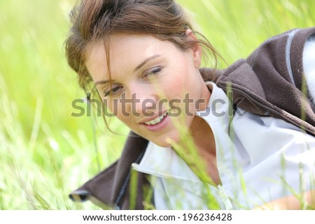 Woman relaxing in country field by sunny day
