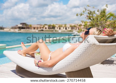 Woman relaxing in deck chair by the pool - stock photo
