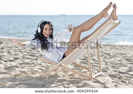 Woman relaxing in deck chair by the sea on a sunny day - stock photo