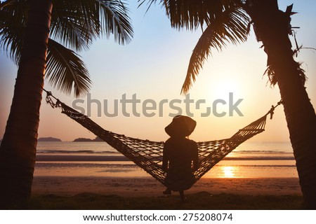woman relaxing in hammock at sunset on the beach, enjoy the life  - stock photo