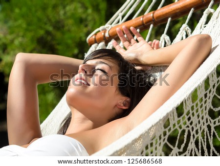 Woman relaxing in hammock for siesta outdoors. Beautiful woman and lying down and relax in garden on summer. . - stock photo