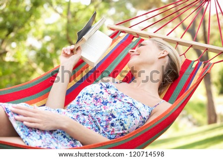 Woman Relaxing In Hammock With Book - stock photo