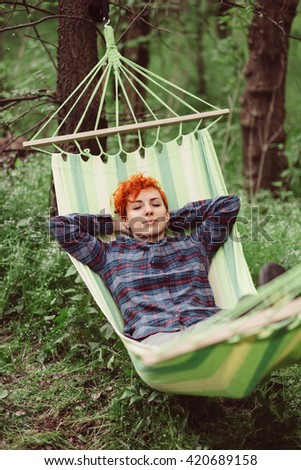 Woman relaxing in hammock. Young caucasian girl with red hair swinging and resting in a hammock in a pleasant laziness of a summer outdoor weekend. Outdoor, adventures and nature vacation.  - stock photo