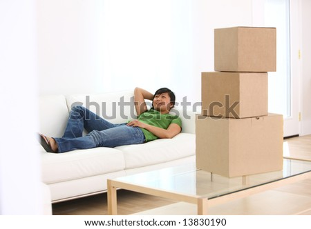 Woman relaxing in living room with boxes