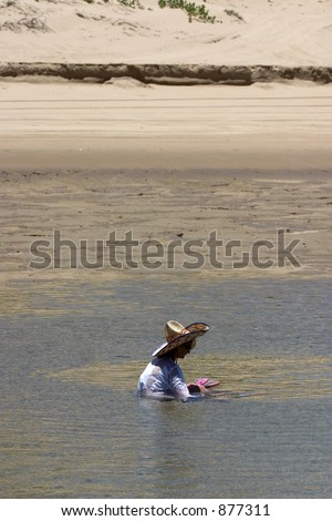 Woman relaxing in pool of water with large funny hat