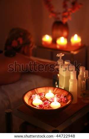 woman relaxing in spa salon in the dark (dish in focus) - stock photo