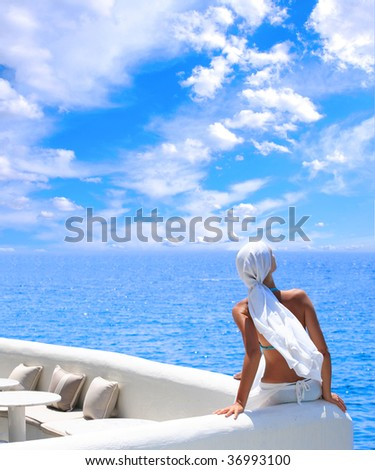 woman relaxing in the afternoon by the sea in Santorini Greece - stock photo