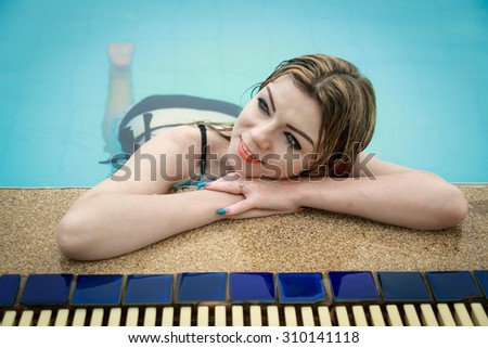 Woman relaxing in the water at swimming pool - stock photo