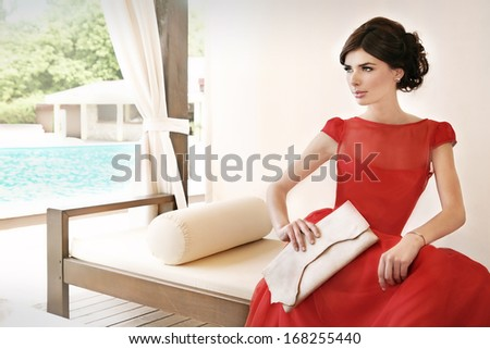 Woman relaxing near pool, waiting on a date, dressed in red, elegant, silk dress. - stock photo