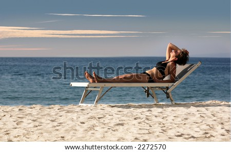 Woman relaxing on a beach looking at the sky