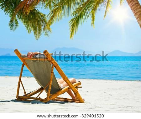 Woman relaxing on a beautiful white beach. - stock photo
