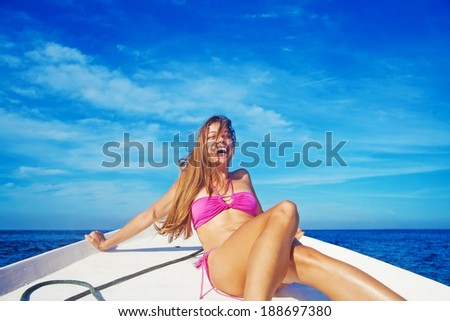 Woman relaxing on a boat and laughing - stock photo