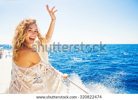 woman relaxing on a cruise boat on windy sunny day - stock photo