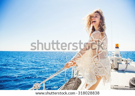 woman relaxing on a cruise boat wearing knitted dress - stock photo