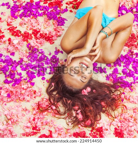 woman relaxing on a flower petals - stock photo