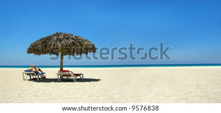 woman relaxing on a lounger reading a book at a tropical beach panorama - stock photo