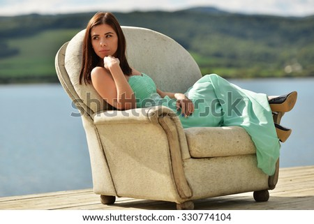 woman relaxing on armchair at beach - stock photo