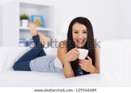 Woman relaxing on couch with cup of coffee - stock photo