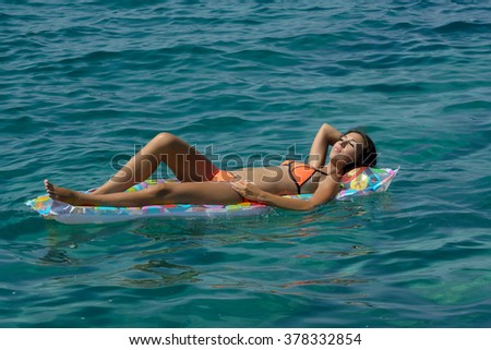 Woman relaxing on inflatable beach mattress in the sea