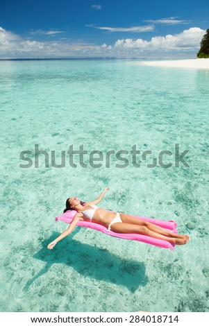 Woman relaxing on inflatable mattress in the sea - stock photo