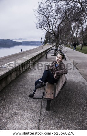 Woman relaxing on park bench in Coeur d'Alene, Idaho.