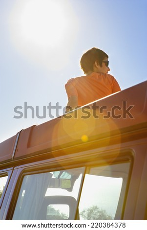 Woman relaxing on roof of car - stock photo