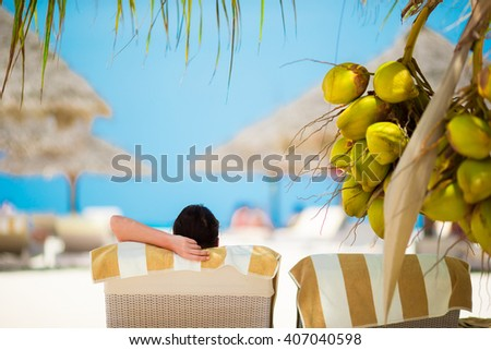 Woman relaxing on sun lounger under a coconut tree - stock photo
