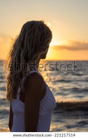Woman relaxing on sunset sea, back torso - stock photo