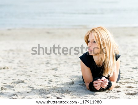 Woman relaxing on the beach after a workout - stock photo