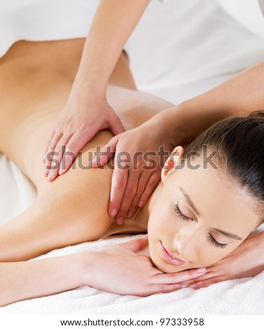 Woman relaxing on the salon and having massage on her shoulder - vertical