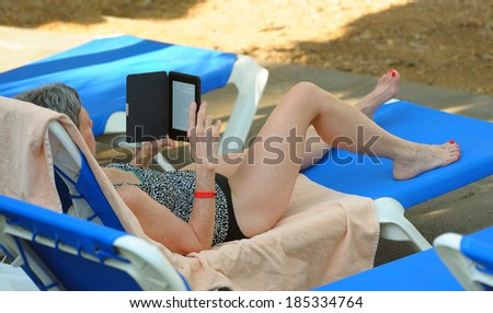 Woman relaxing on vacation with e-reader at poolside - stock photo