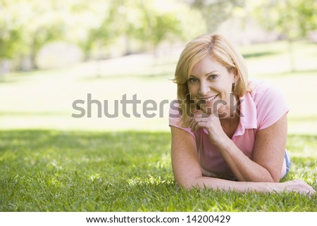 Woman relaxing outdoors smiling - stock photo