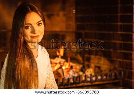 Woman relaxing resting at fireplace. Young girl heating warming up. Winter at home. - stock photo