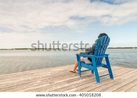 Woman relaxing seated near the ocean.