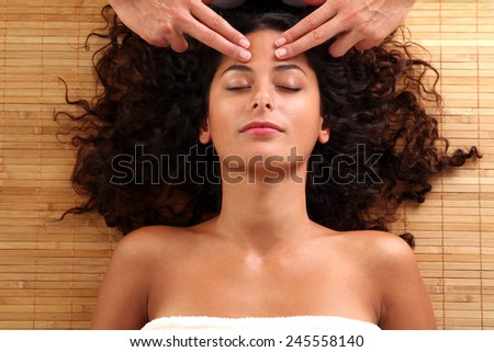 woman relaxing while a hot stone massage - stock photo