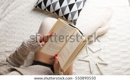 Woman relaxing with a book at her home. Lifestyle concept photo