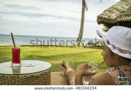 Woman relaxing with fresh drink by the ocean at island in Thailand.