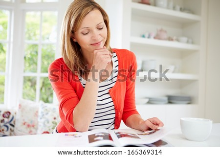 Woman Relaxing With Magazine At Home - stock photo