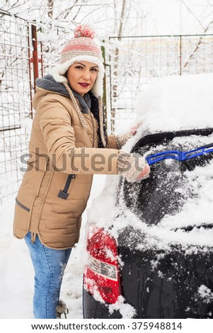 Woman remove snow from car in cold day - stock photo