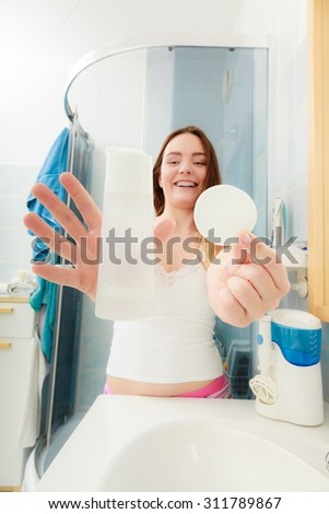 Woman removing makeup with cotton swab pad. Young girl taking care of skin. Skincare concept.