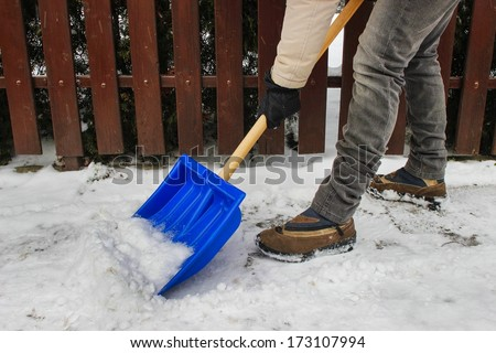 Woman removing snow from the sidewalk after snowstorm - stock photo