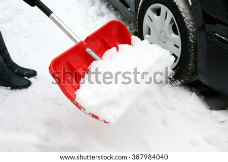 Woman removing snow with snow shovel beside car