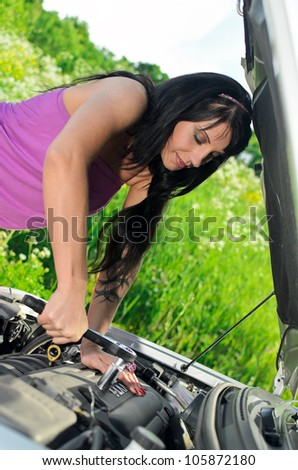Woman repairing broken car with a socket spanner wrench. - stock photo