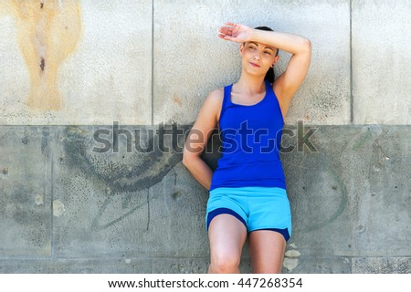 Woman resting after run by the wall. Outdoor. - stock photo