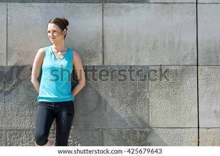 Woman resting after run by the wall urban.