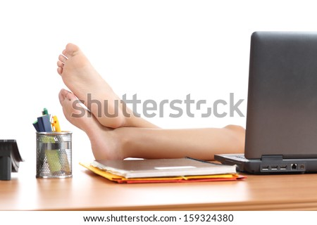Woman resting at work with the feet over the office table isolated on a white background           - stock photo